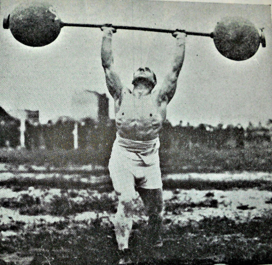 vintage man strongman lifting heavy barbell overhead press