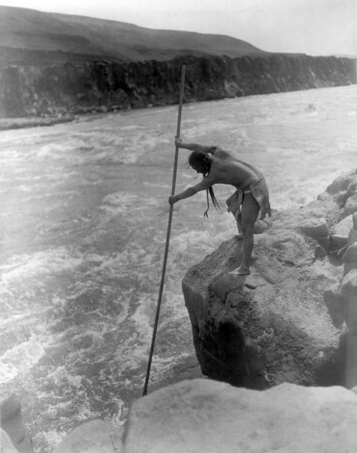 Vintage native american man fishing in large river with spear.