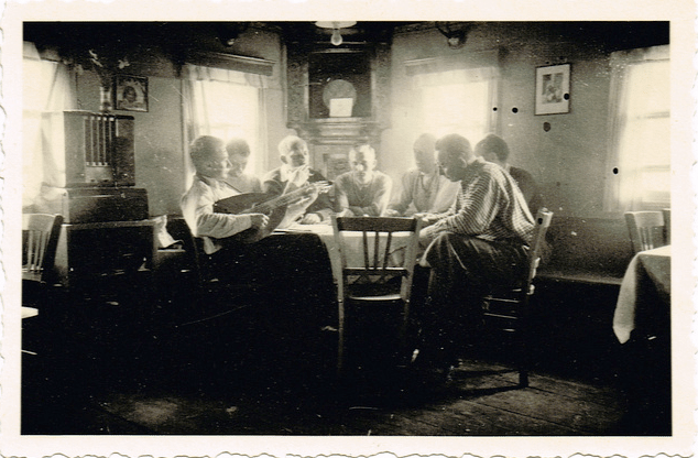 Vintage men sitting at dinner table talking.