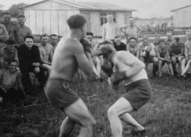 Vintage men fighting boxing in field.