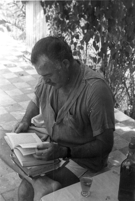 Ernest Hemingway is reading book outside at table.