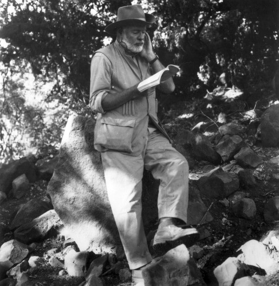 Ernest Hemingway is reading book & siting on rock.