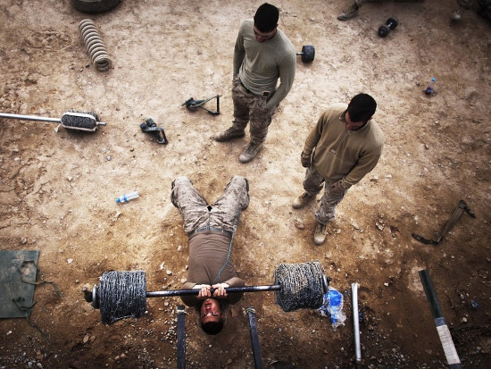 soldier lifting improvised barbell overhead shot