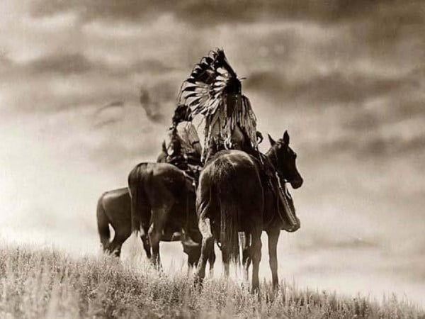 native american men riding horses in field