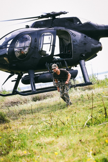 Man getting out of helicopter for hunting trip expedition.