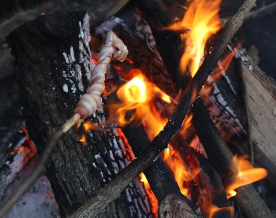 bacon cooking on stick over fire