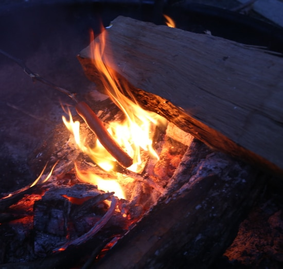 hot dog cooking on stick over fire