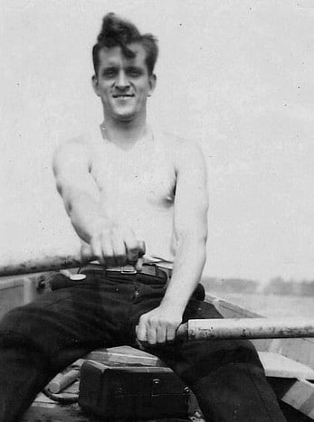 man in rowboat rowing oars wearing wife beater tank top