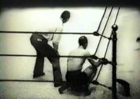 vintage boxer sitting in corner of ring with trainer