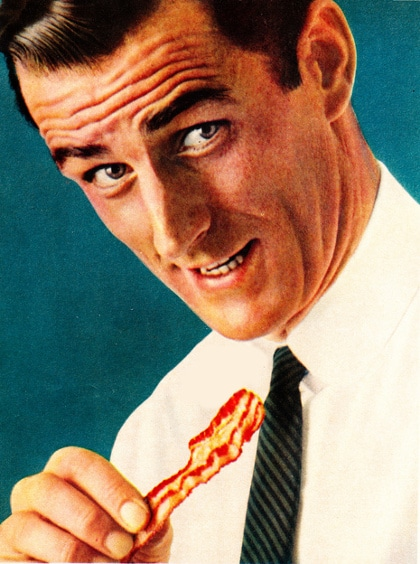 A man eating bacon and wearing shirt and tie.