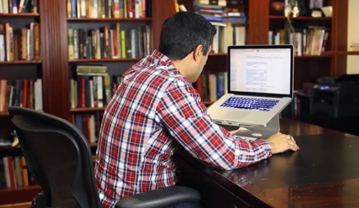 man slouching at home office desk