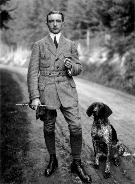 Vintage hunter on road with pointer dog wearing sporting jacket.