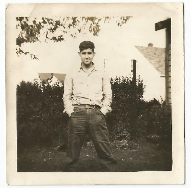 Vintage man standing in yard with hands in pockets.