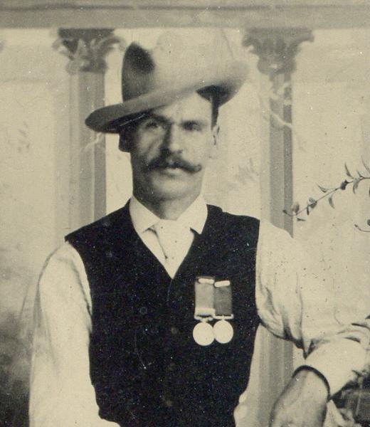 A man with hat and mustache on face.