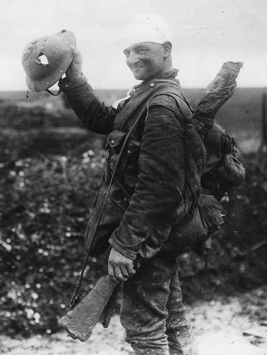 A soldier holding up helmet with bullet fire.