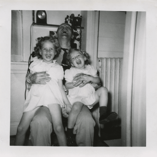 vintage father laughing with children daughters