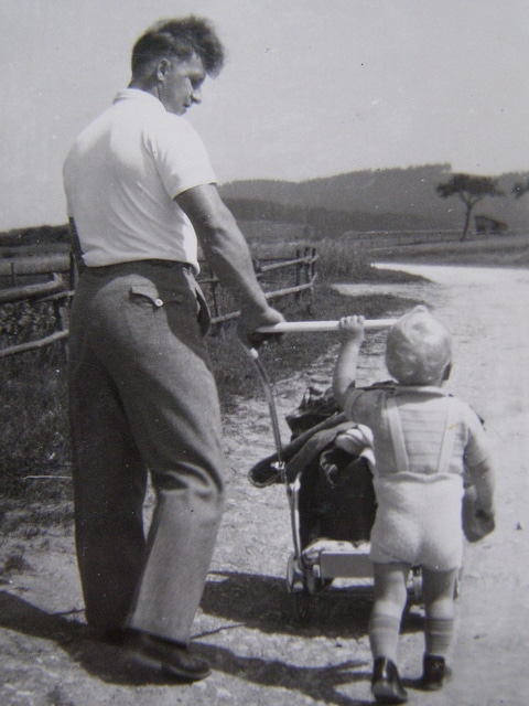 Vintage 1950s father walking with baby child.