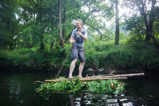 man on log raft floating in river