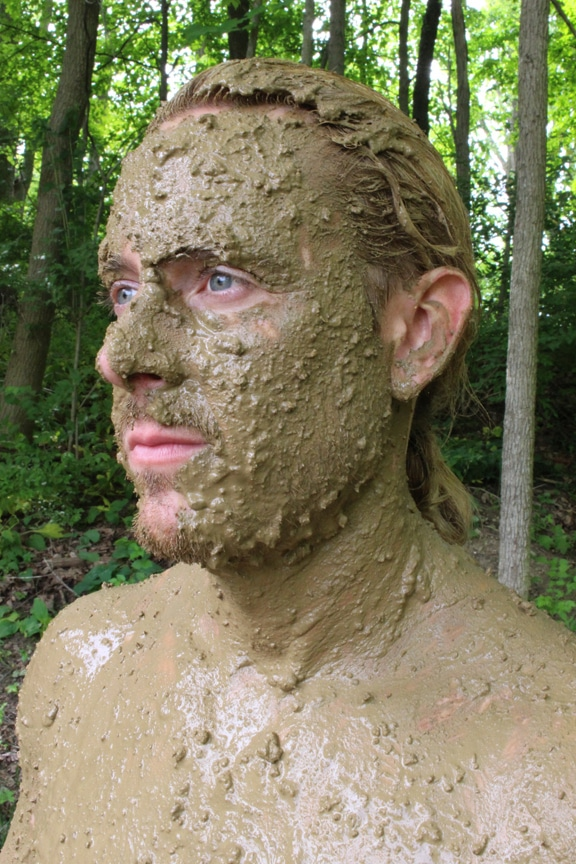 Man face covered in mud for camouflaging.