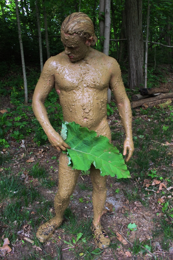 Man's full body covered in mud for camouflaging.