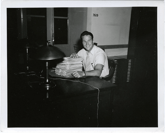 Vintage man on desk with stack of paperwork.