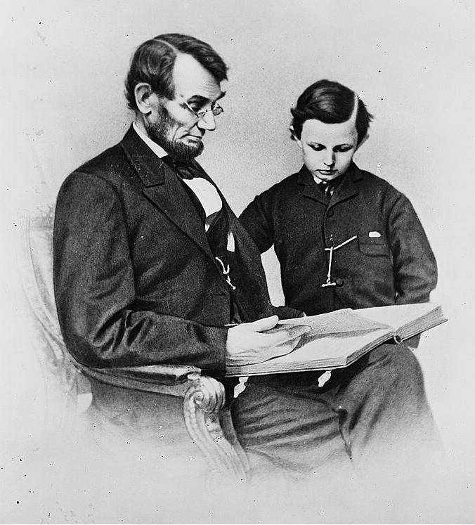 Abraham Lincoln reading with son.
