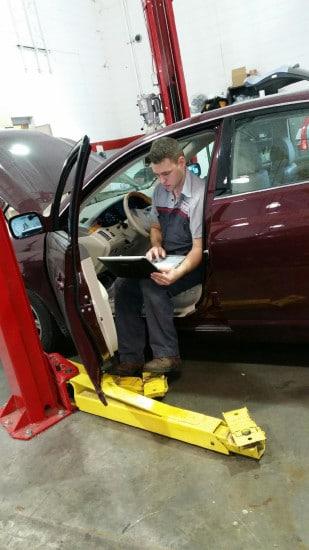 car auto mechanic technician diagnosing problem computer