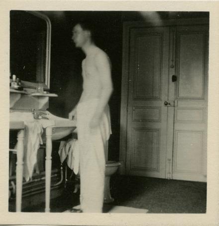 vintage young man looking in mirror washroom bathroom