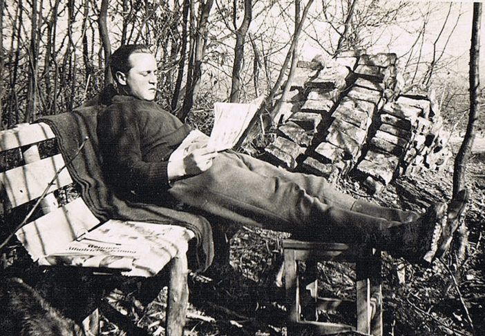 vintage man reading newspaper on bench in woods