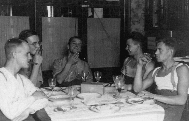 Vintage young guys at dinner table with Cigars.