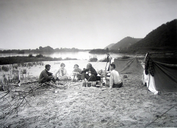 vintage group of people camping on sand bank river