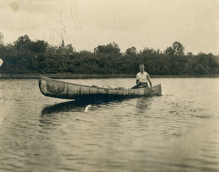 vintage man in canoe paddling on lake