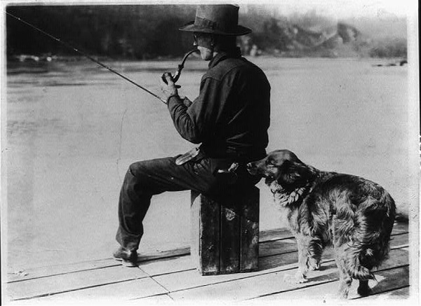 vintage man fishing off dock with dog and smoking pipe