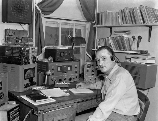 vintage man at desk with ham amateur radio equipment