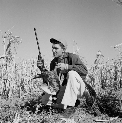 vintage man hunting in corn field dead pheasant in hand