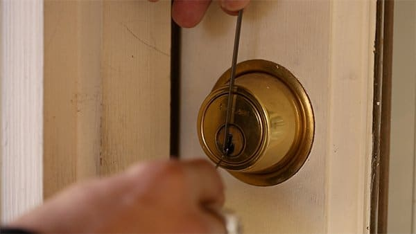 close up picking a lock pin tumbler deadbolt