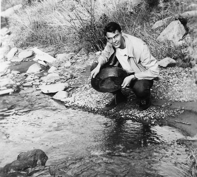 vintage man gold panning prospecting on small stream