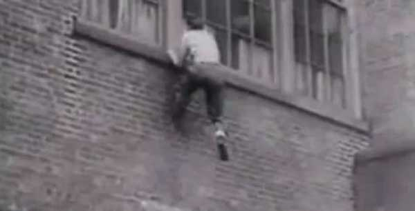 vintage man scaling climbing brick wall parkour