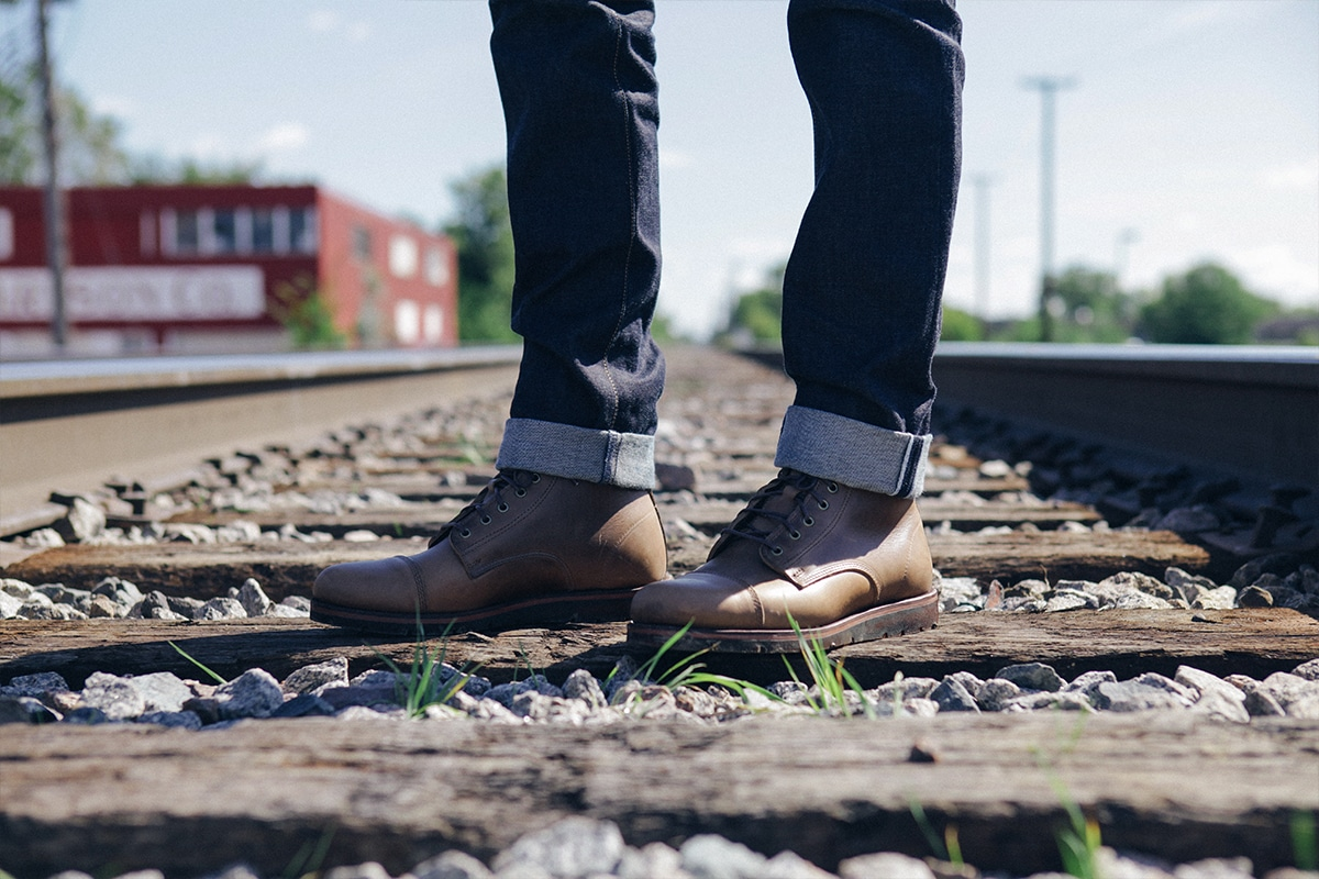 Brown leather boots with rolled up jeans with train tracks.