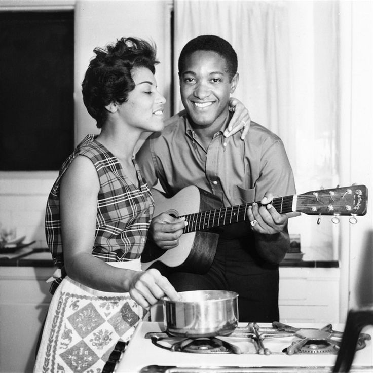 vintage african american couple cooking playing guitar in kitchen