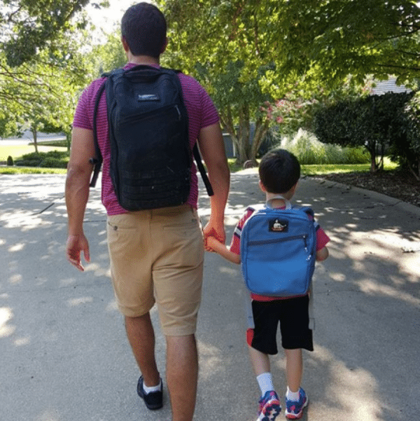 dad walking with son down street with backpacks