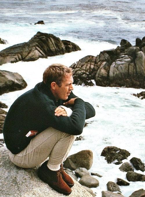 steve mcqueen sitting on rock next to ocean