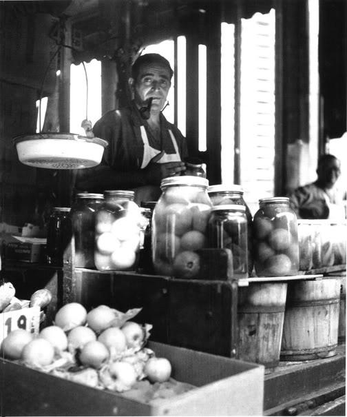 Vintage man store owner pickling vegetables smoking pipe.