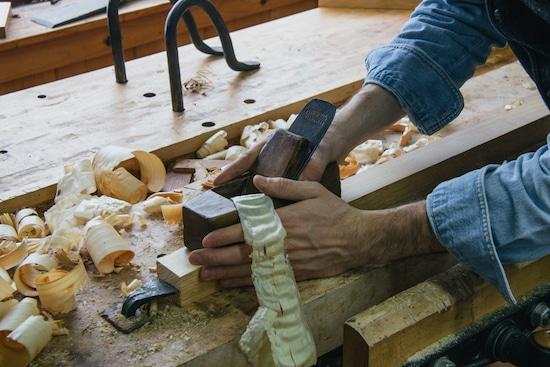 man craftsman using hand plane on wood
