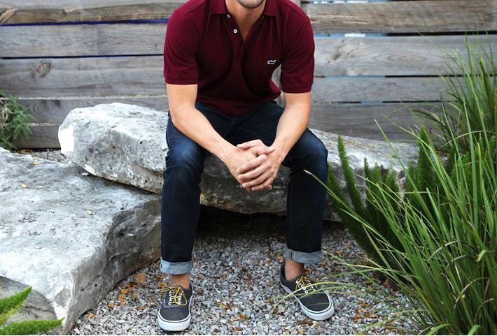 Man wearing polo shirt  sitting on a rock.