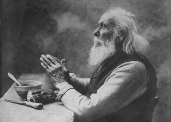 vintage old bearded man praying saying grace at dinner table