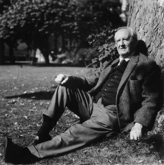 Vintage J.R.R. Tolkien sitting on ground against tree.