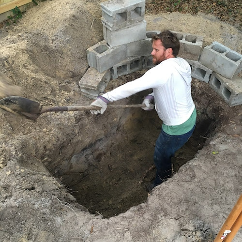 A man digging a square shape grave with blocks.