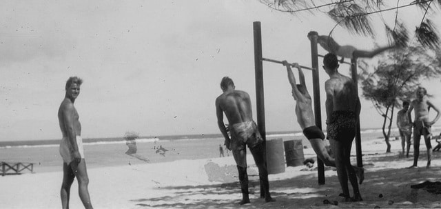 vintage men on beach doing pull ups on vacation