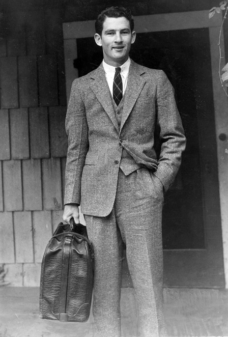 Vintage man in suit leaving home with suitcase in hand.